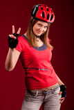 Young woman cyclist shows OK Royalty Free Stock Images