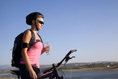 Young woman cyclist with a water bottle. Young woman cyclist with  water bottle  after a long journey Royalty Free Stock Images