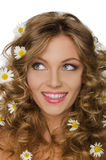 Young woman with daisies in curly hair looks away Royalty Free Stock Photography