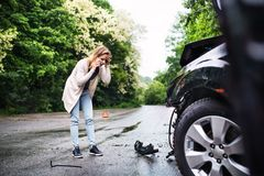 Young woman by the damaged car after a car accident, making a phone call. Royalty Free Stock Photo