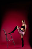 Young woman in dance sport costume kick chair Stock Photo