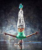 Young woman dancer. Young woman hip-hop dancer standing on head on wall background royalty free stock image