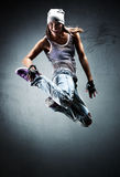 Young woman dancer jumping. On wall background Stock Photos