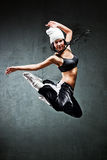 Young woman dancer jumping. On wall background stock images