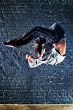 Young woman dancer jumping. On wall background royalty free stock photo