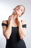 Young woman in dancer's leotard stretching neck. On white background stock image