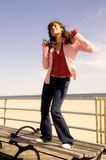 Young woman dancing. On a bench near the seaside Stock Photography