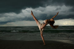 Young woman dancing on a beach. On a storm day at the sunset Royalty Free Stock Image