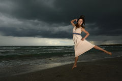 Young woman dancing on a beach. On a storm day at the sunset Stock Photography