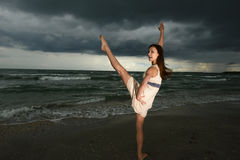 Young woman dancing on a beach. On a storm day at the sunset Royalty Free Stock Photo