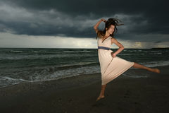 Young woman dancing on a beach. On a storm day at the sunset Royalty Free Stock Images