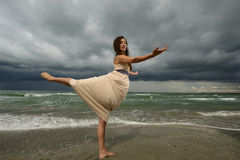Young woman dancing on a beach. On a storm day at the sunset Royalty Free Stock Photography