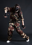 Young woman dancing in camouflage. Over dark background royalty free stock photography