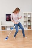 Young woman dancing while cleaning floor Royalty Free Stock Photography