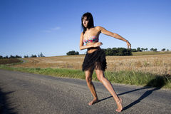 Young woman dancing on a country road. Royalty Free Stock Image