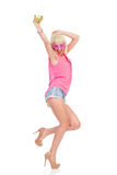 Young woman dancing with a drink Stock Images
