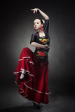 Young woman dancing flamenco with castanets on black Stock Images
