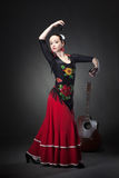 Young woman dancing flamenco with castanets on black Stock Photos