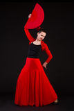 Young woman dancing flamenco with fan. Over black background Stock Photography