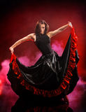 Young woman dancing flamenco on smoke background Royalty Free Stock Images