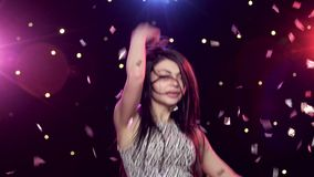 Young woman dancing in front disco style lights glitter confetti. Pretty young woman dancing in front of disco style lights and glitter Confetti. Close-up stock video