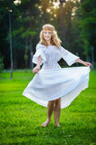 Young woman dancing on green fresh grass in a park Royalty Free Stock Images