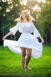 Young woman dancing on green fresh grass in a park Royalty Free Stock Photos