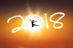 Young woman dancing with number 2018. Silhouette of young woman dancing in the golden sky while while celebrating new year of 2018 Royalty Free Stock Photo