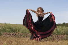 Young woman dancing outdoors in long skirt Stock Photo