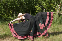 Young woman dancing outdoors in long skirt Stock Images
