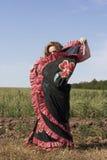 Young woman dancing outdoors in long skirt Stock Photos
