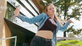 Young Woman Dancing Outside. A young woman dancing outside. Long shot stock footage