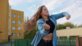 Young Woman Dancing Outside. A young woman dancing outside. Medium shot stock video footage