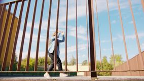 Young Woman Dancing Outside. A young woman dancing outside behind the fence. Long shot stock video footage