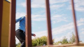 Young Woman Dancing Outside. A young woman dancing outside behind the fence. Medium shot stock footage
