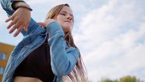 Young Woman Dancing Outside. A young woman dancing outside. Long shot stock video
