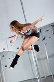Young woman dancing with pole. Young athletic woman dancing around the pole Royalty Free Stock Photography