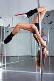 Young woman dancing with pole. Young athletic woman dancing around the pole Stock Images
