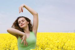 Young woman dancing in rape flower field Royalty Free Stock Photo