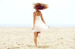 Young woman dancing on the sand at the beach. Portrait of a young woman dancing on the sand at the beach Stock Image