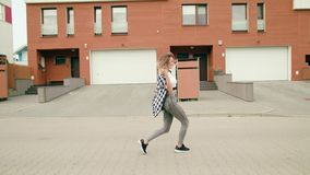 Young woman dancing in the street. A young woman dancing in the street. Long shot. Dolly shot stock footage