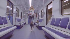 Young woman dancing in subway train. Young woman coming in subway train and starting to dance stock footage