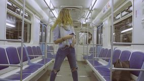 Young woman dancing in subway train stock footage