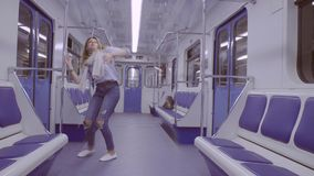 Young woman dancing in subway train stock video footage