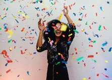 Young woman dancing under confetti at home. Celebrating birthday royalty free stock image
