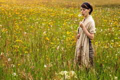 Young woman with a dandelion in a colorful wildflower meadow Royalty Free Stock Image