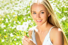 Young woman among dandelions Royalty Free Stock Image