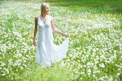 Young woman among dandelions Royalty Free Stock Photo