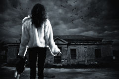 Young woman in dangerous nightwalk. Young woman with doll in front of a haunted house stock image