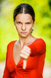 Young woman dangles thumb Royalty Free Stock Images